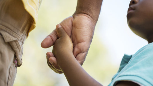 Close-up of child holding fathers hand