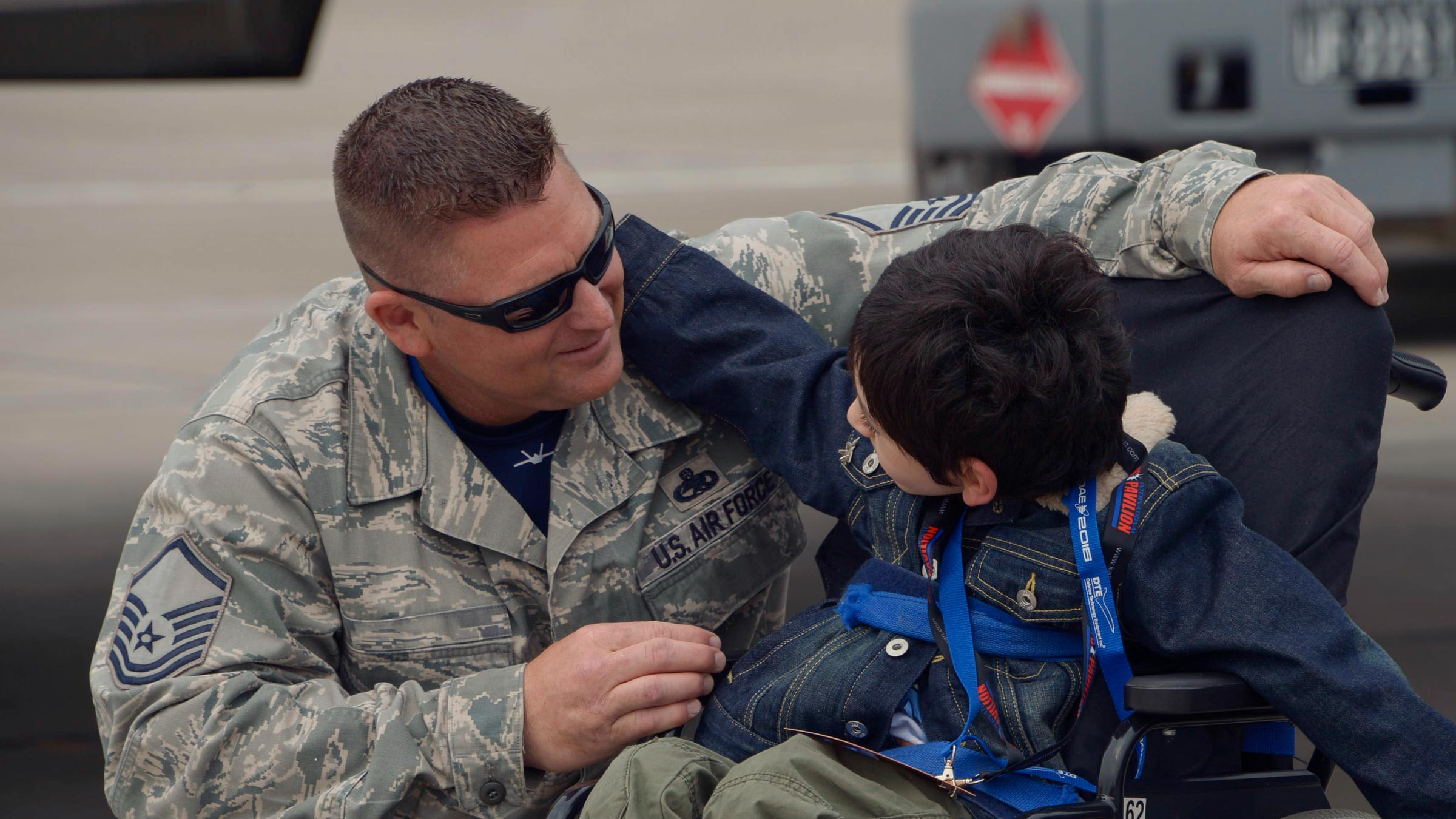 Air force man and boy in a wheelchair talk
