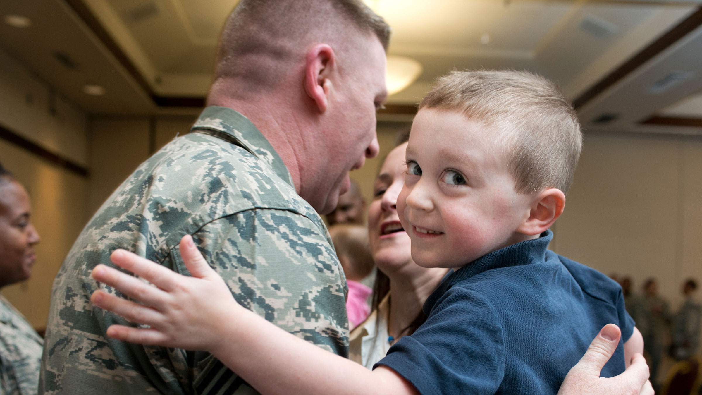 Service member embraces his wife and son.