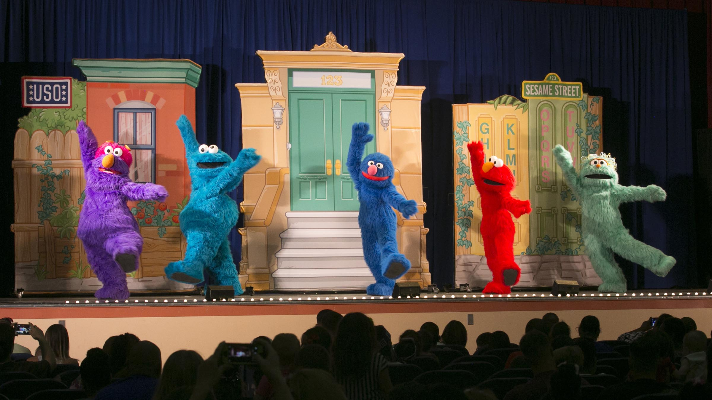 Sesame Street characters dance on stage