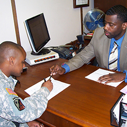 Service provider sitting at a desk, working with a service member.