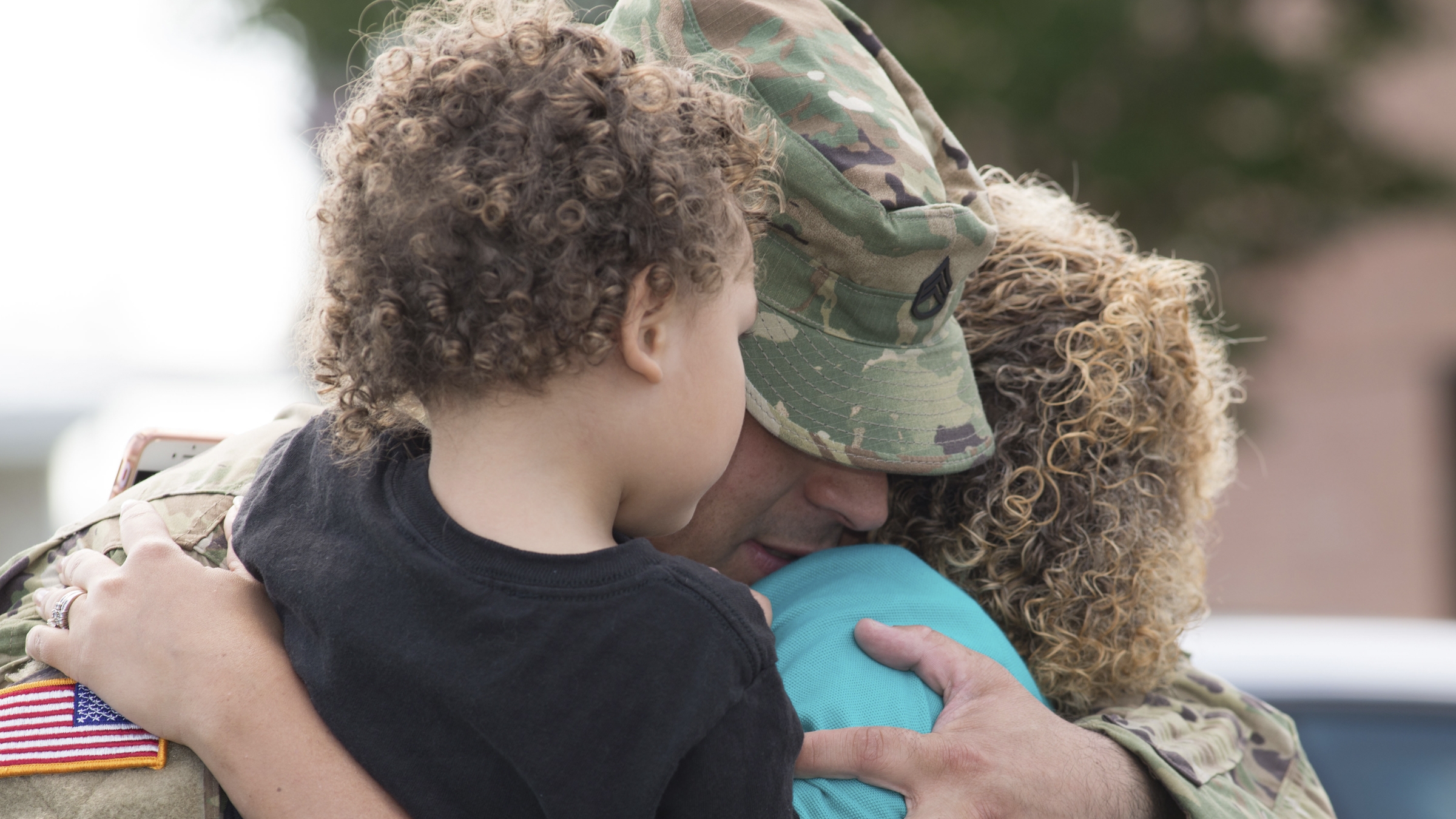 Service Member hugs his young children.