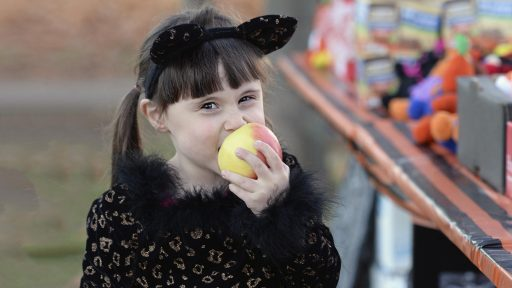 Child wearing halloween costume biting apple