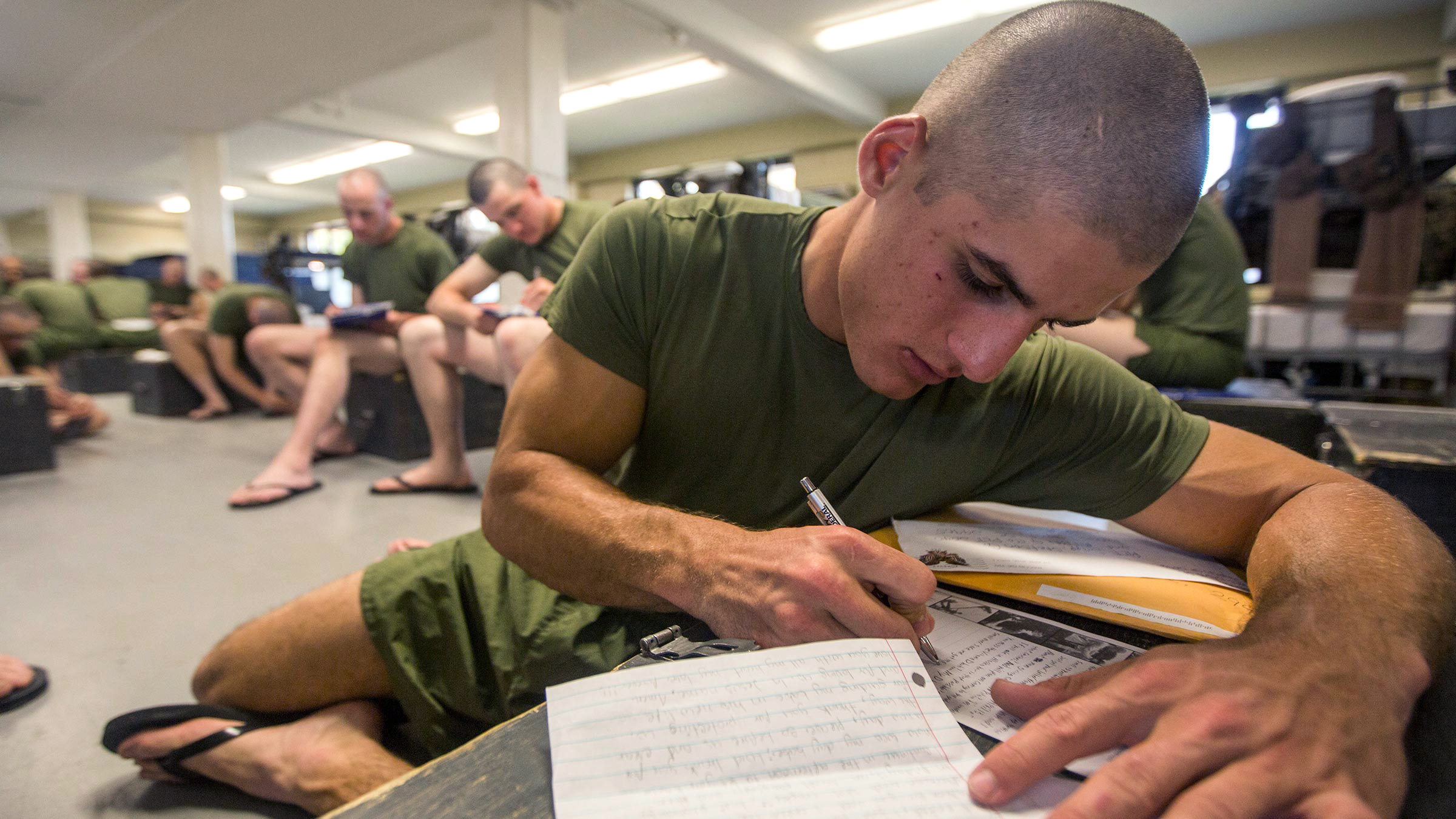 A service member writes letters home during free time