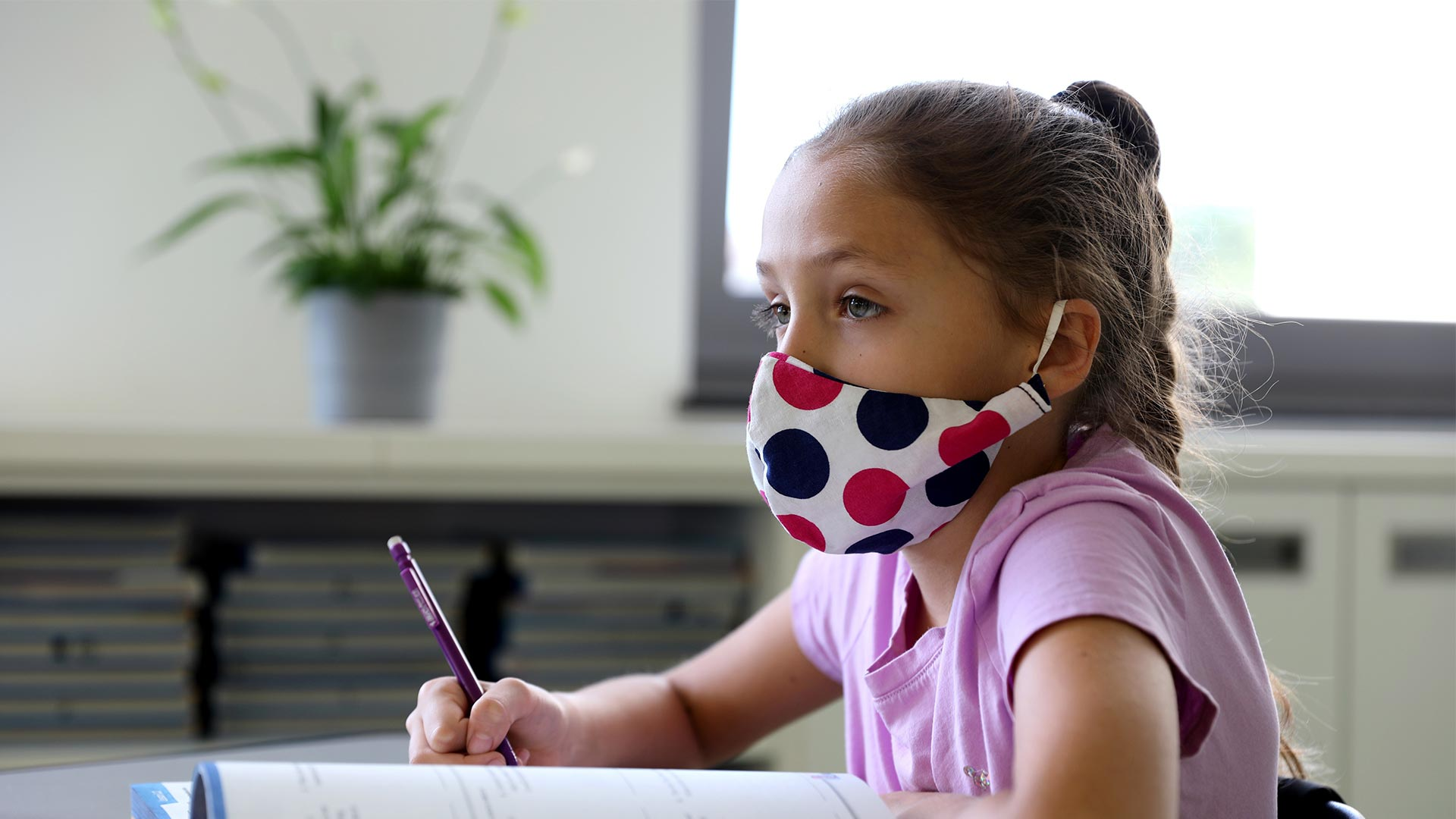Young student wearing mask in class