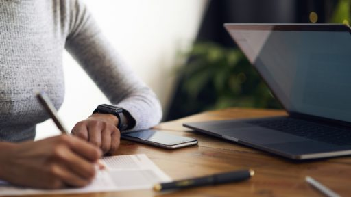Woman filling out paperwork at desk
