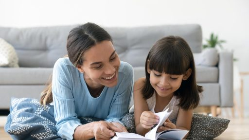 Smiling mother and daughter read together