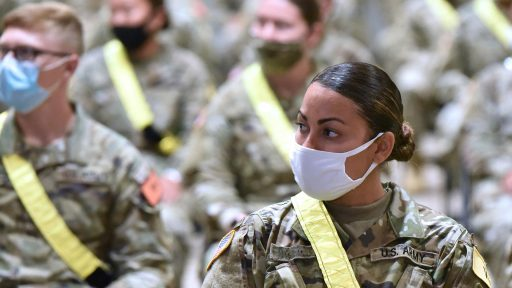 Masked woman soldier in group of soldiers