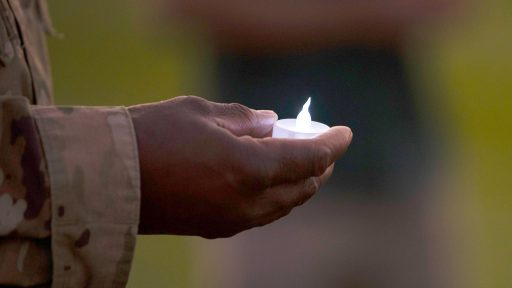 service member holding candle