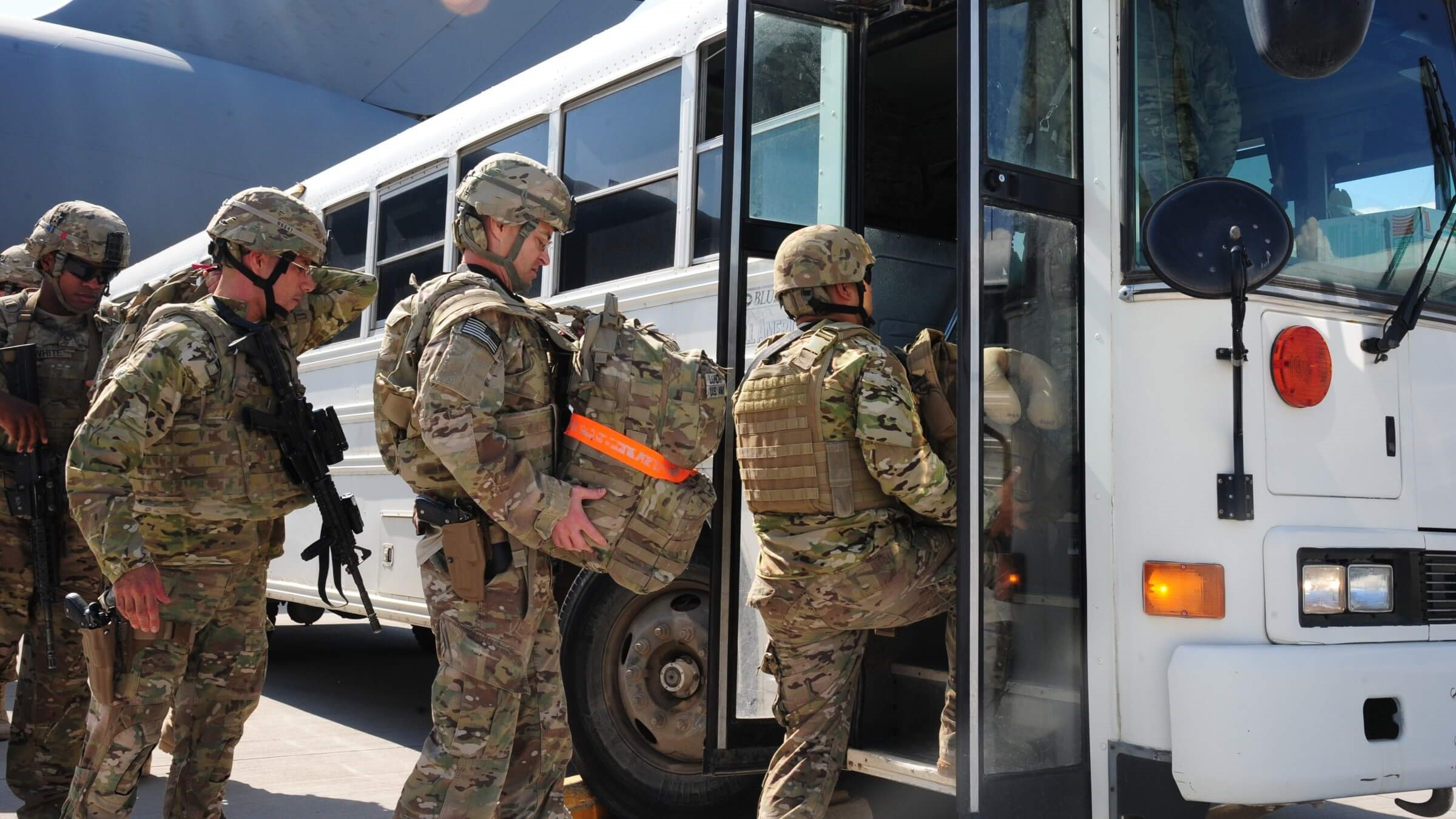 Service members getting on a bus