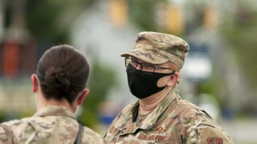 Two service members with face masks talking