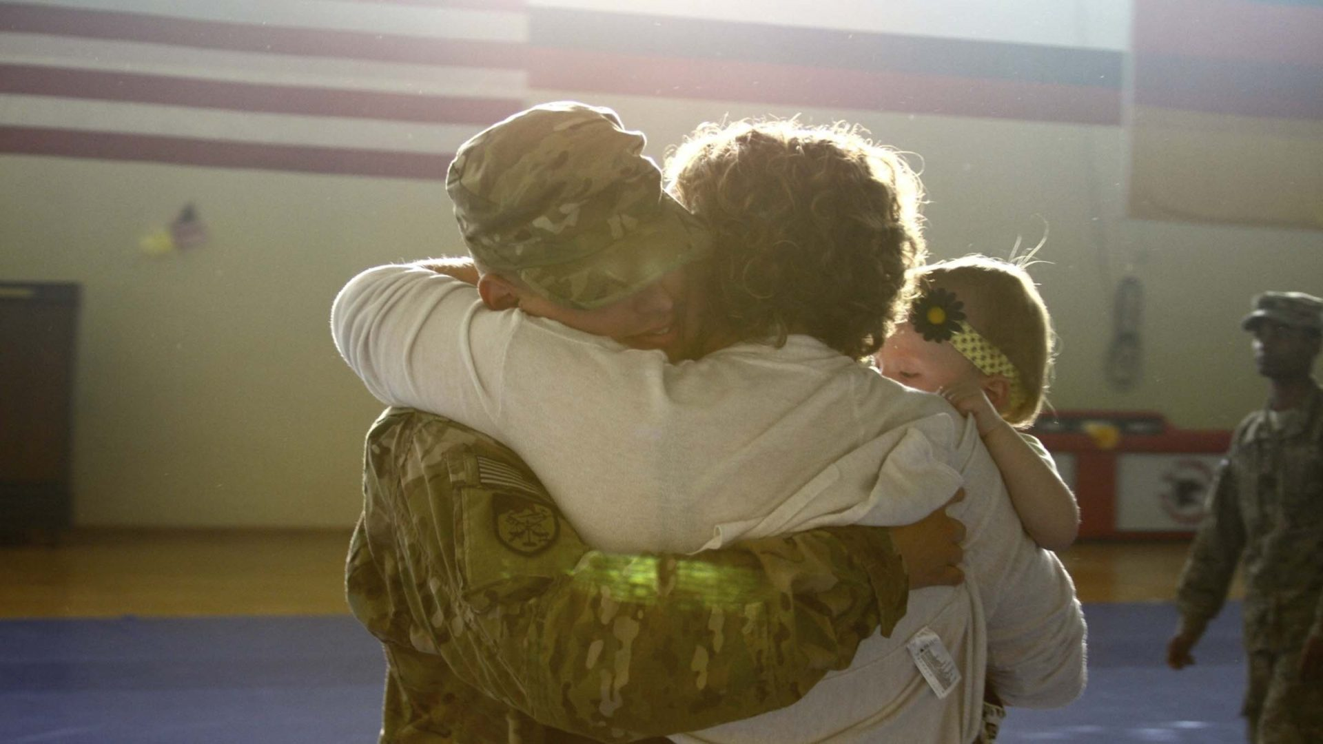 Service member embraces with his wife and child.