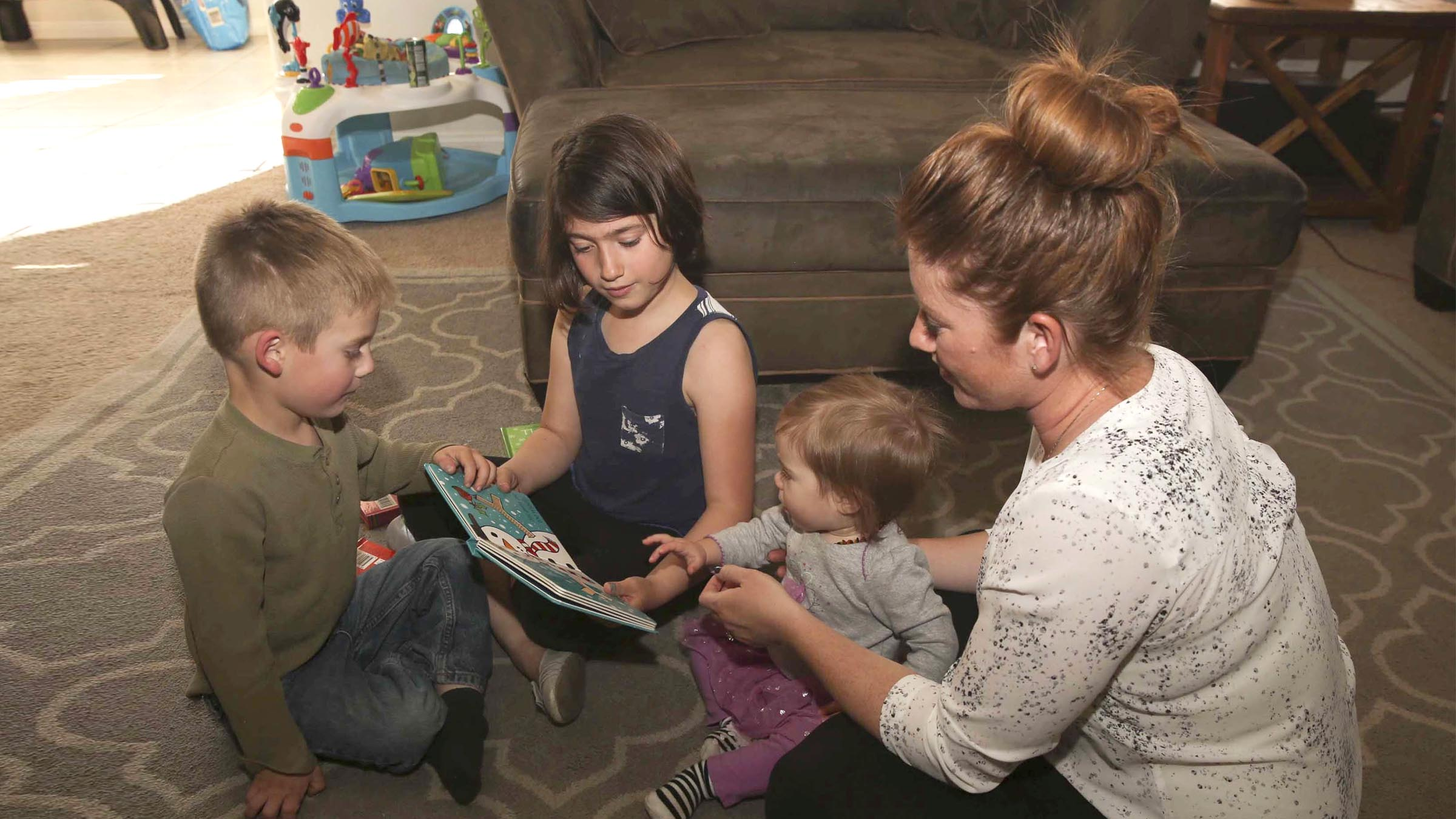 Mother and her children reading a book in the living room.