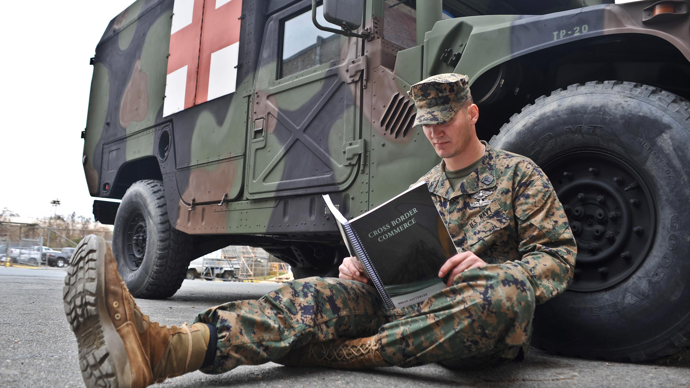 Service member propped up on truck reading