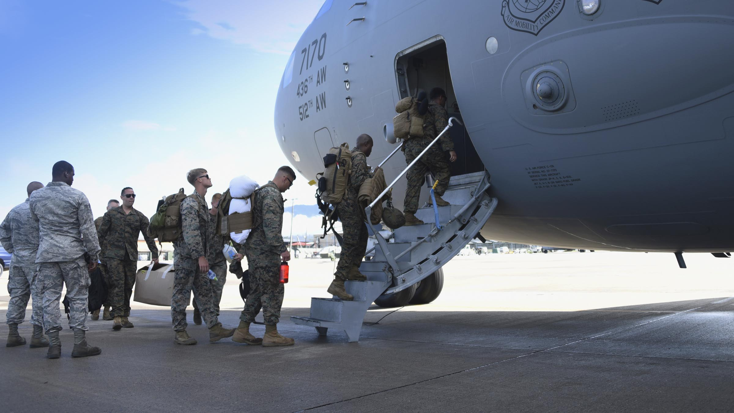 Service members boarding large aircraft