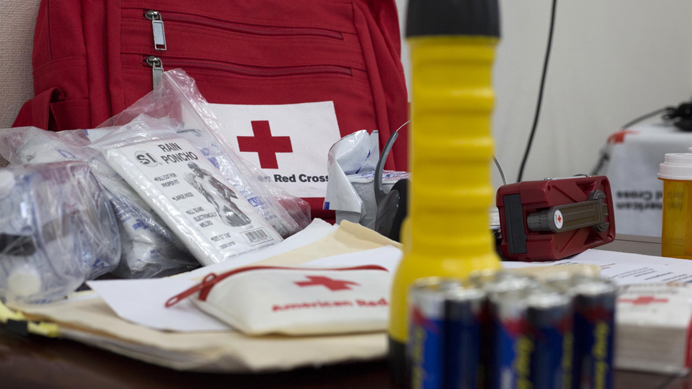 American Red Cross branded First-Aid materials are spread across a table.