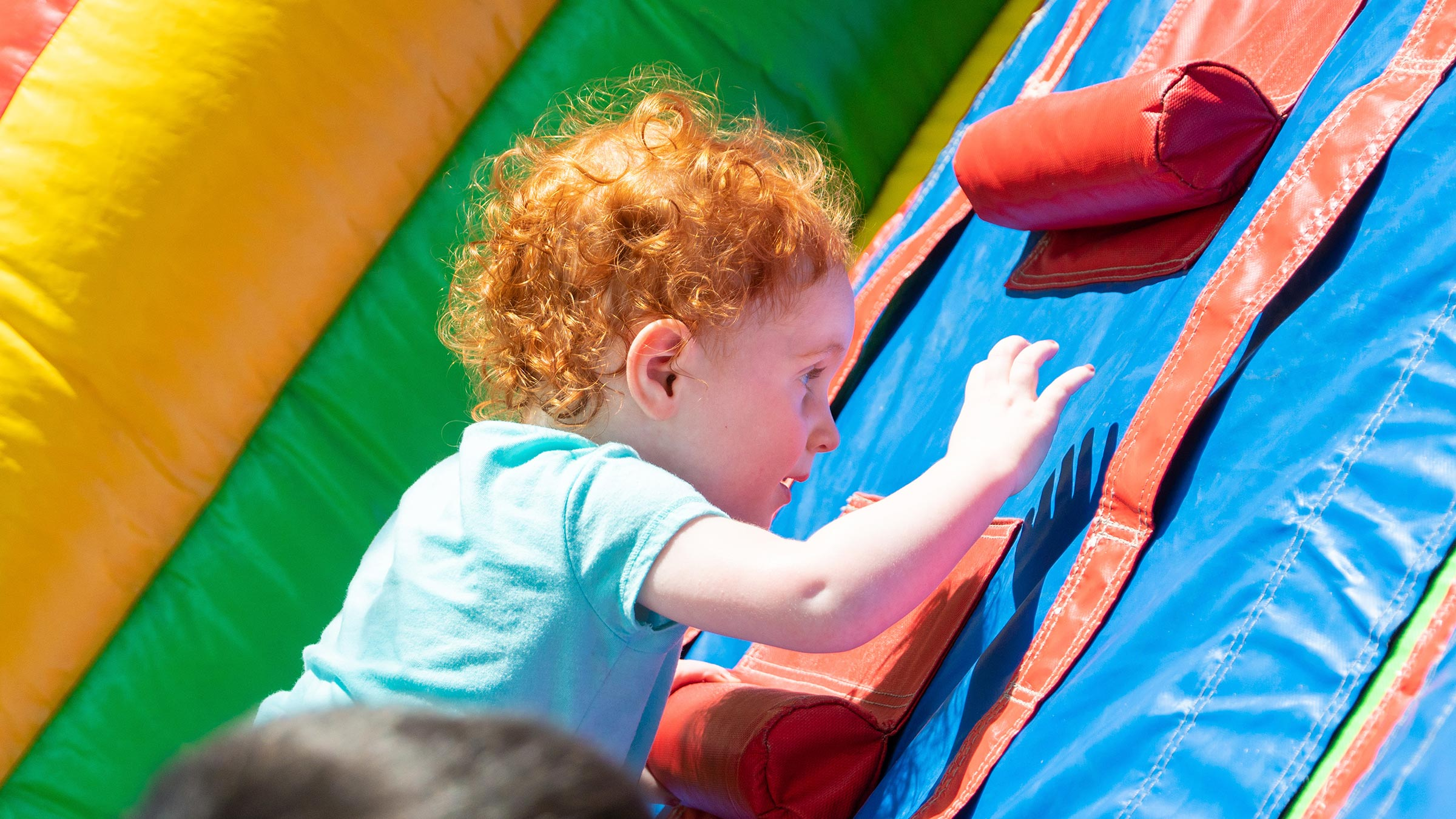 Child climbs on inflatable obstacle