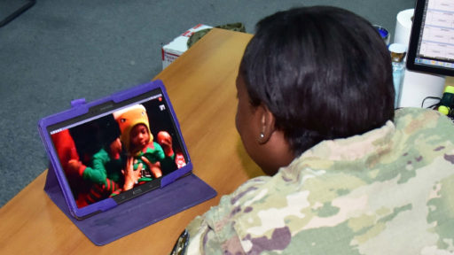 Service member watches their children open presents via video chat.
