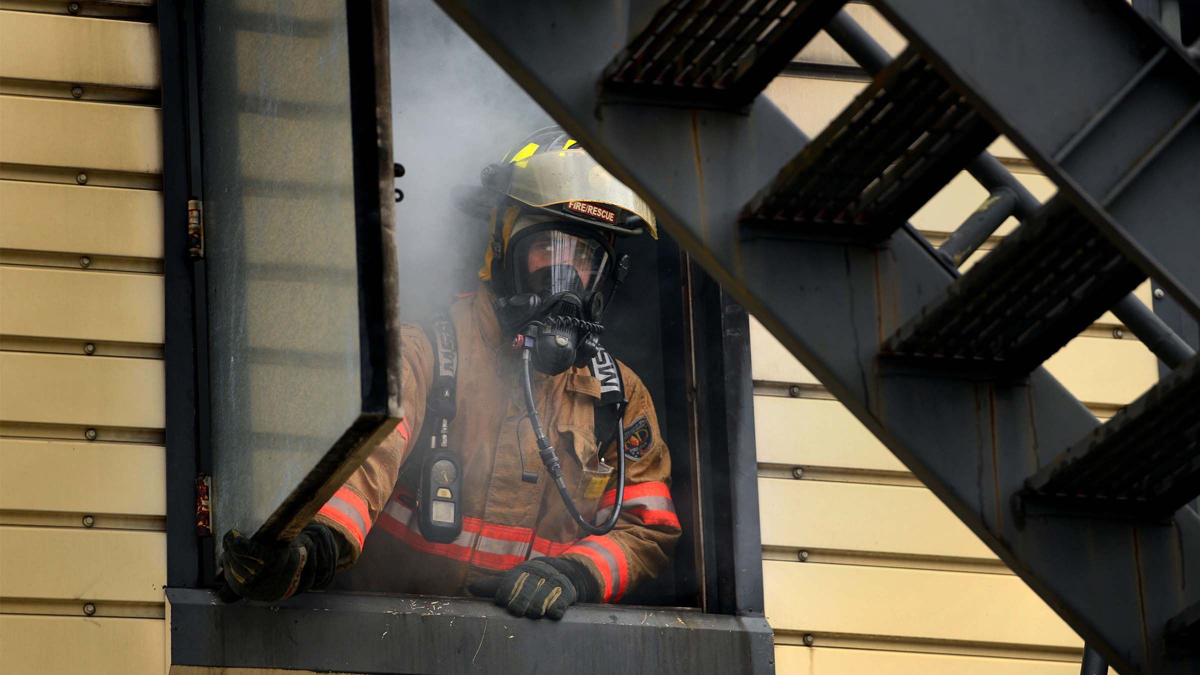Firefighter looking out of a smoke filled window