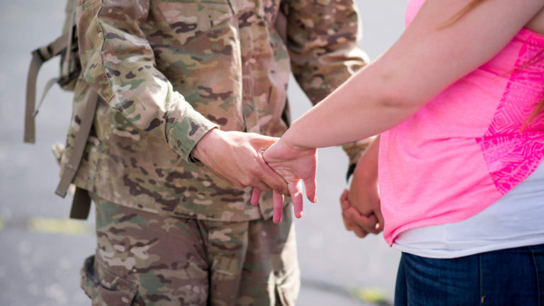 Service member holding hands with military spouse.