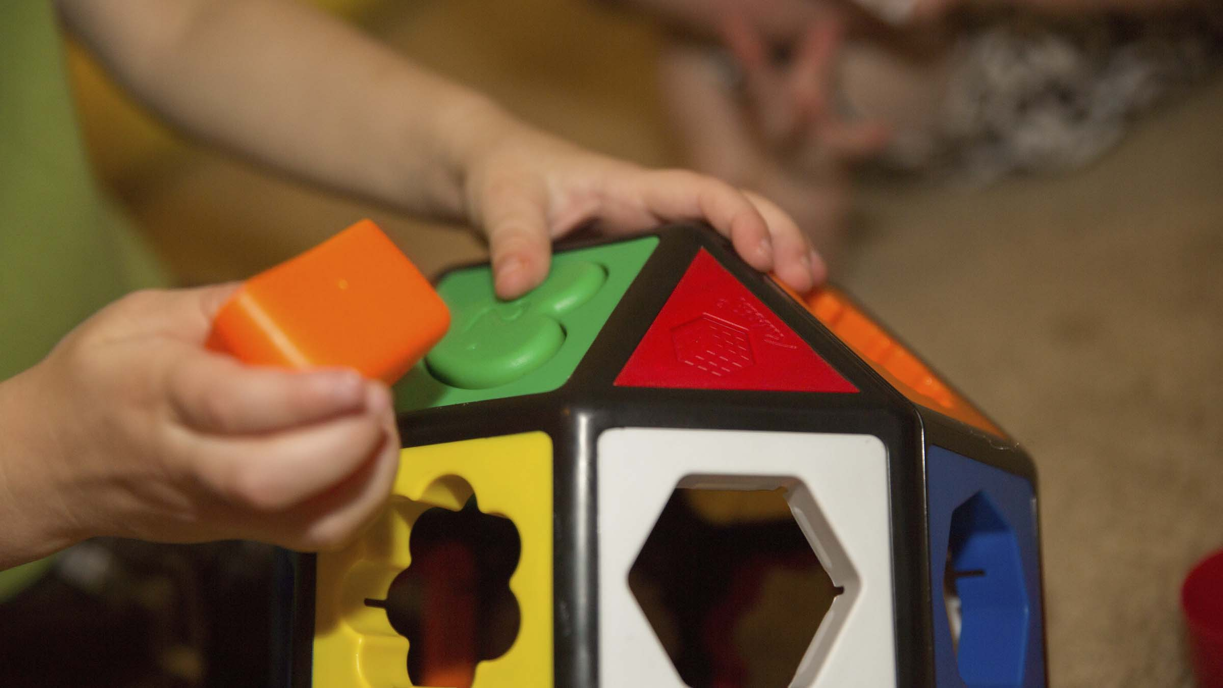 A child's hands playing with an educational toy