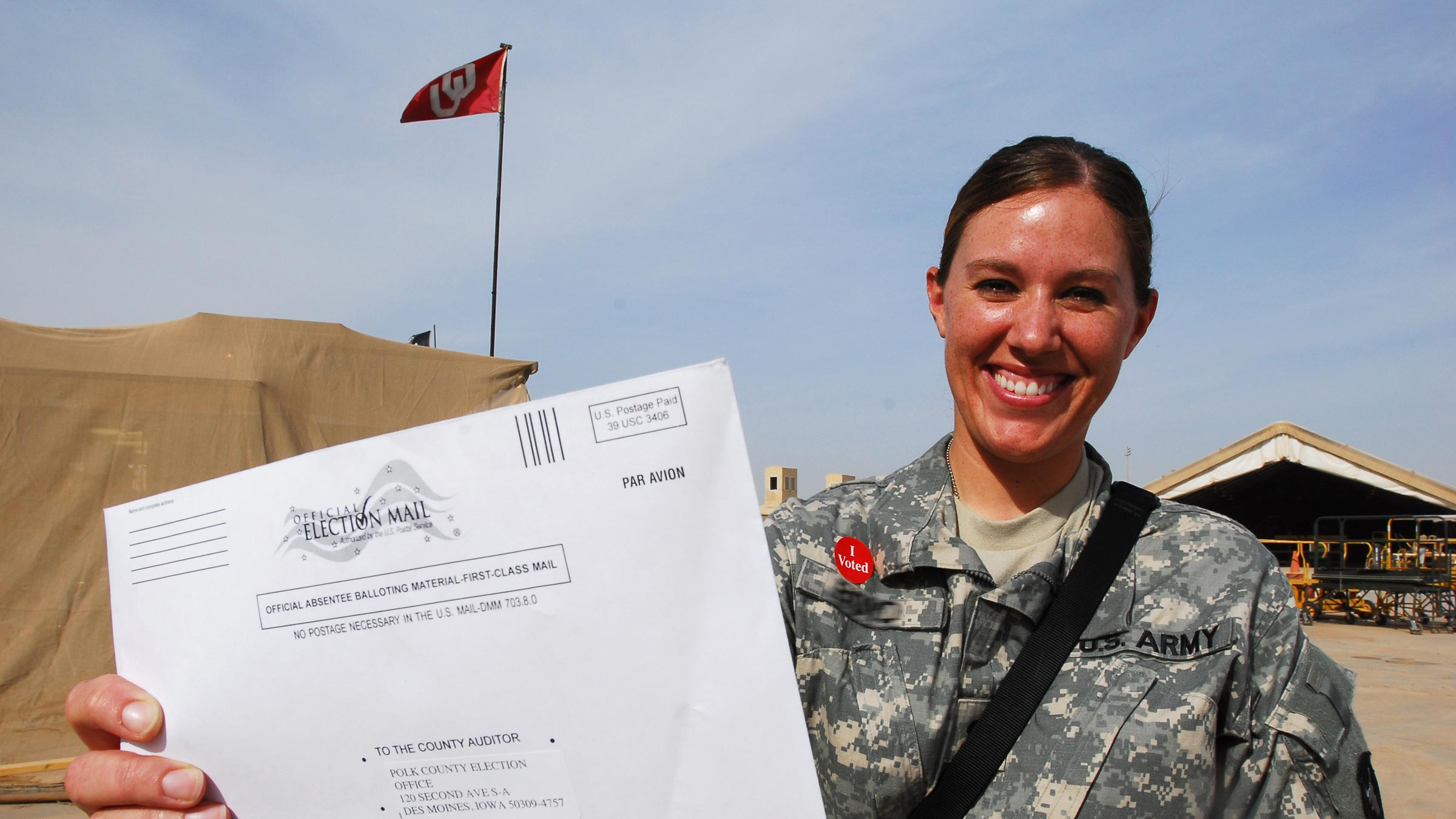 Service member holds up voting ballot