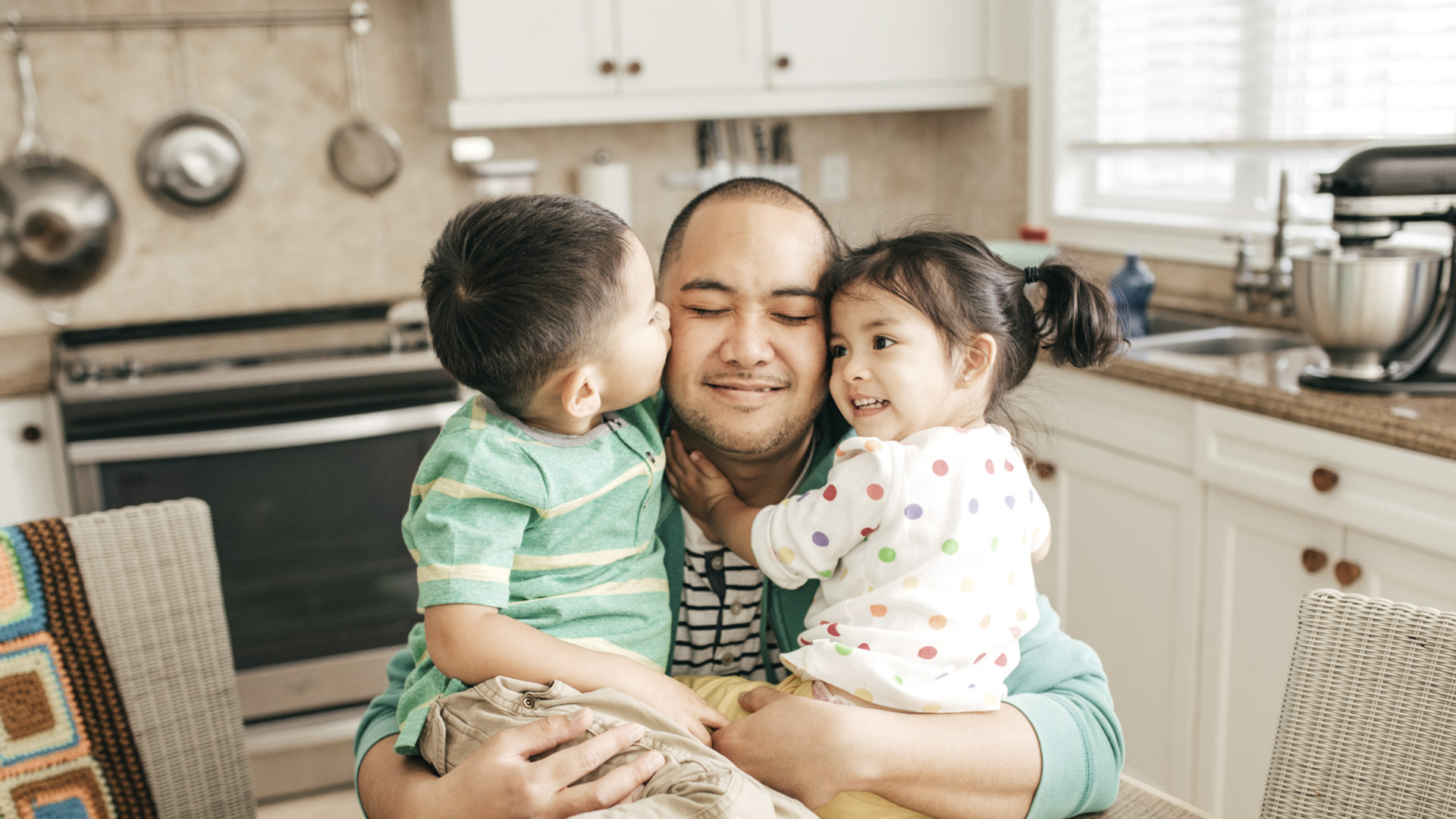 A father hugging two children in the kitchen
