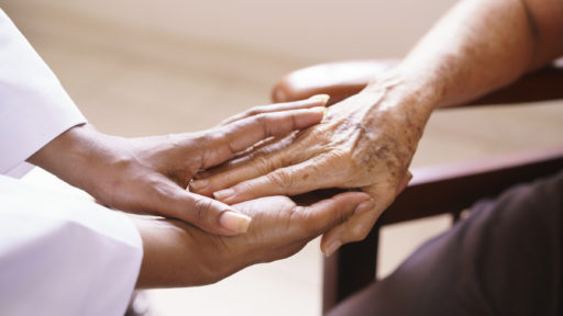 The hands of an elderly woman being held by younger hands.