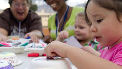 Young children and their caregivers make arts and crafts together