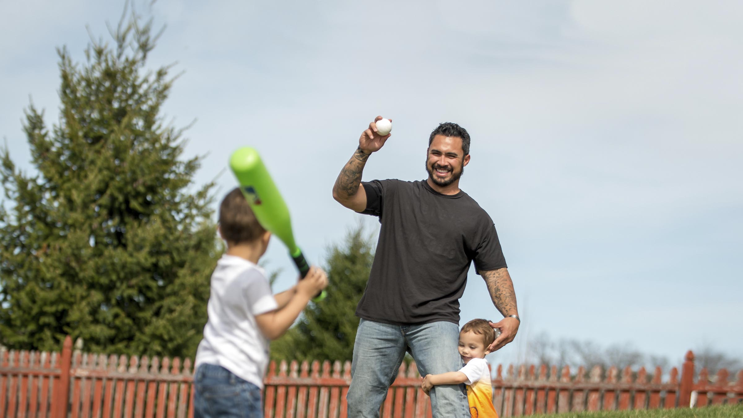 Dad playing baseball in backyard with kids