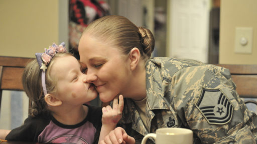 Girl kissing service member mom