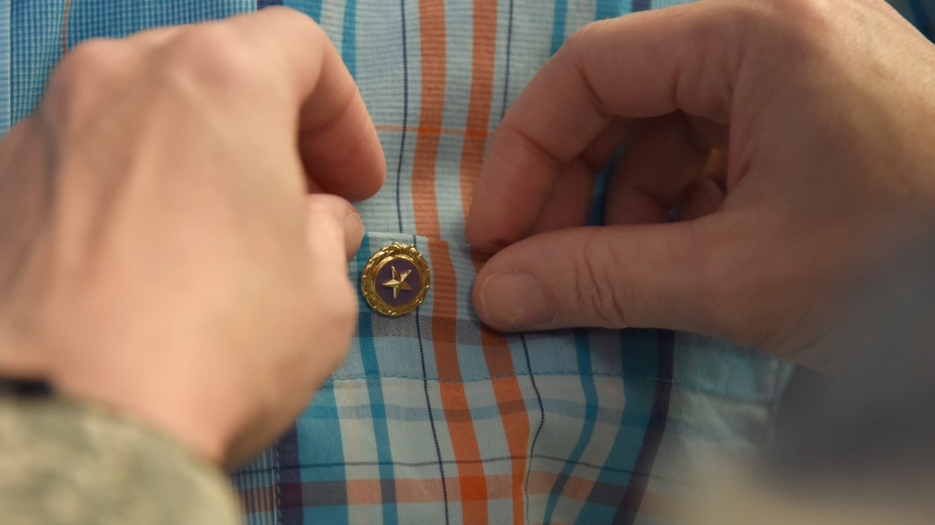 Fastening a gold star pin on a shirt