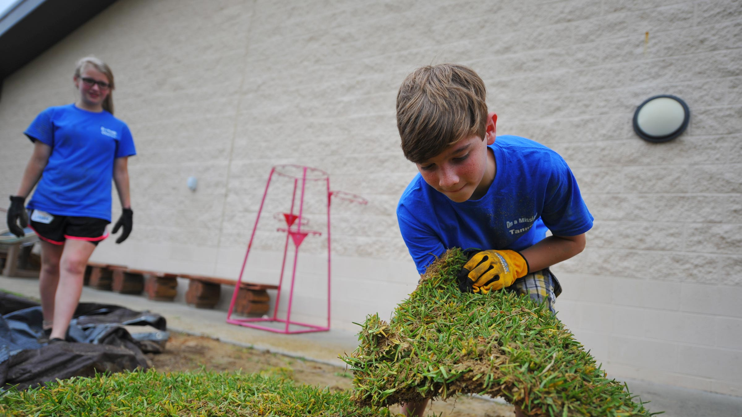 Two youths work laying sod