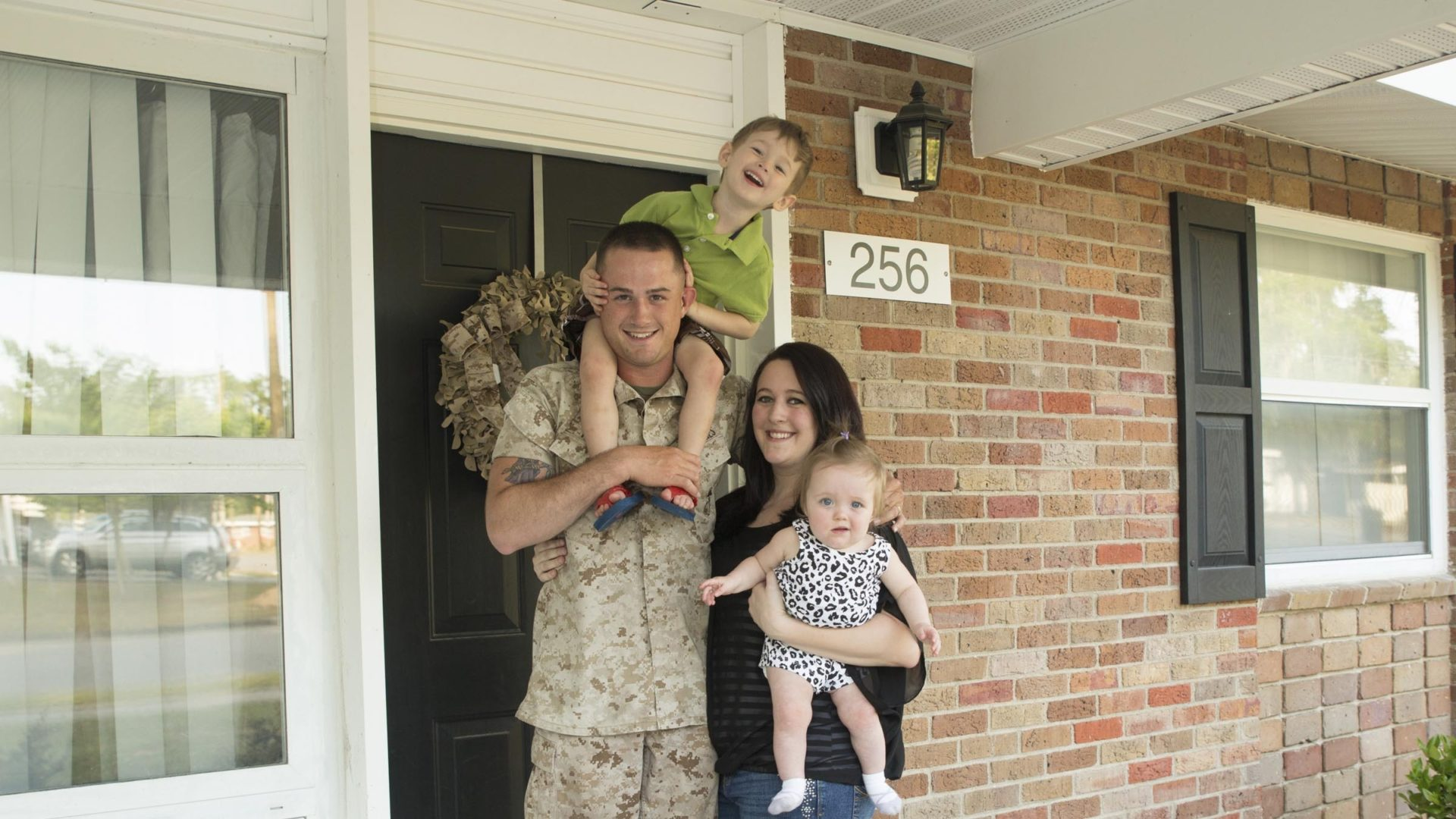 Family standing outside front door of home
