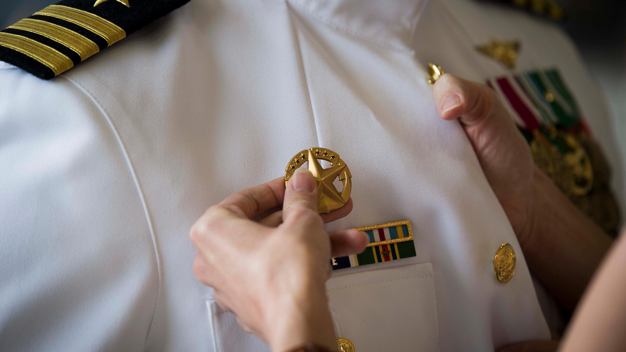 Wife pins insignia on military husband