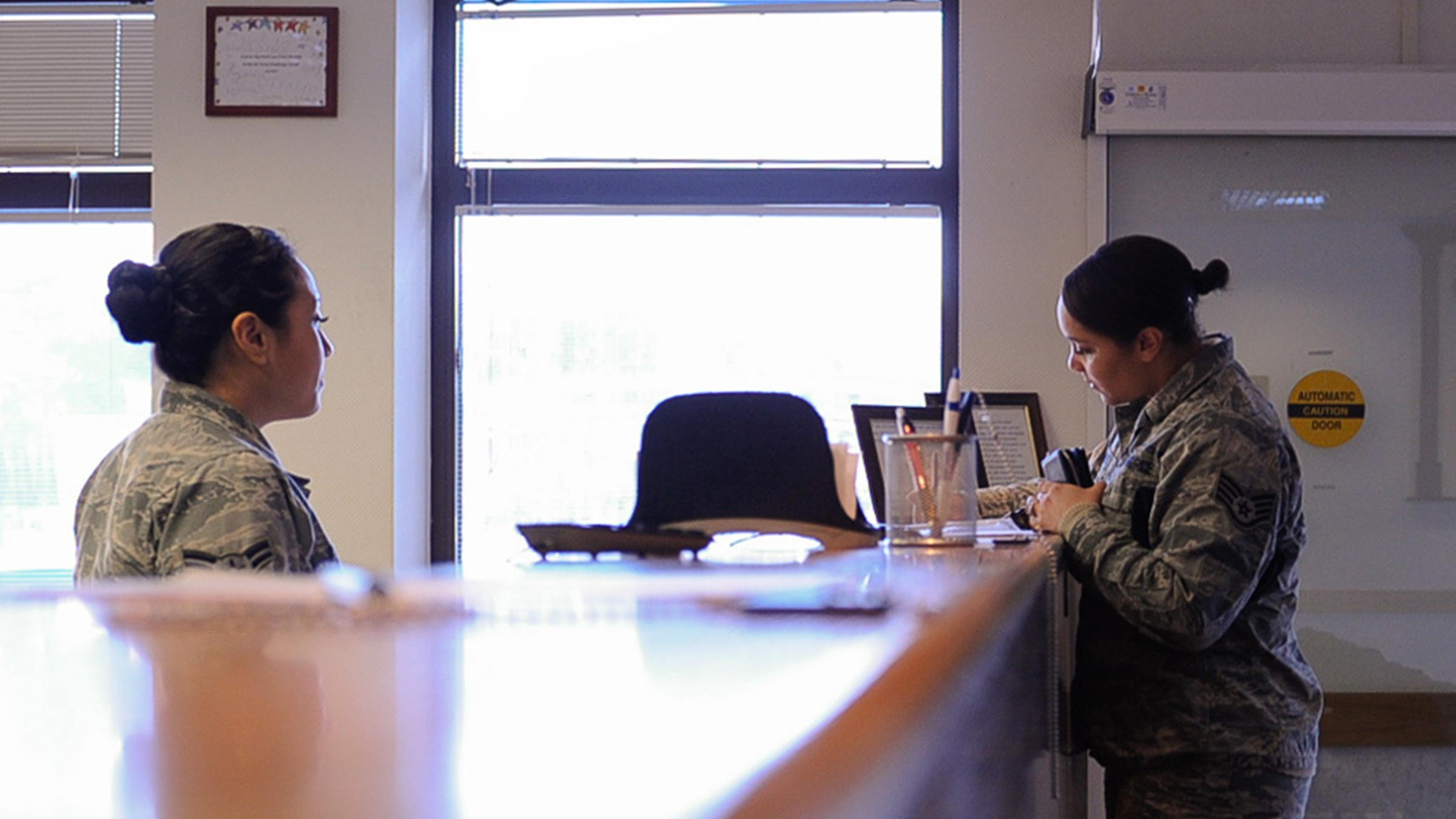 Service member helps another with paperwork.