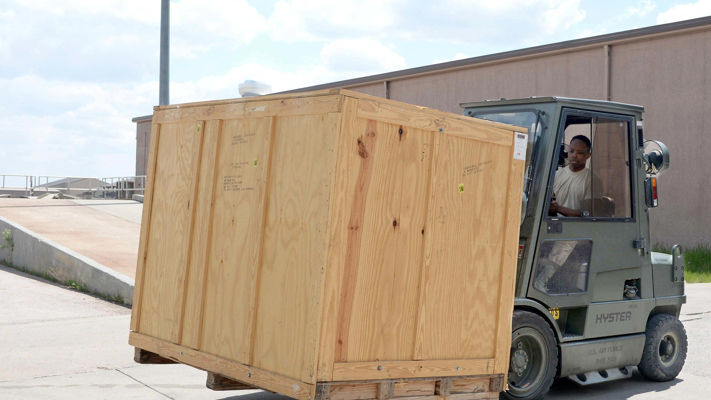 Fork lift carries wooden moving box