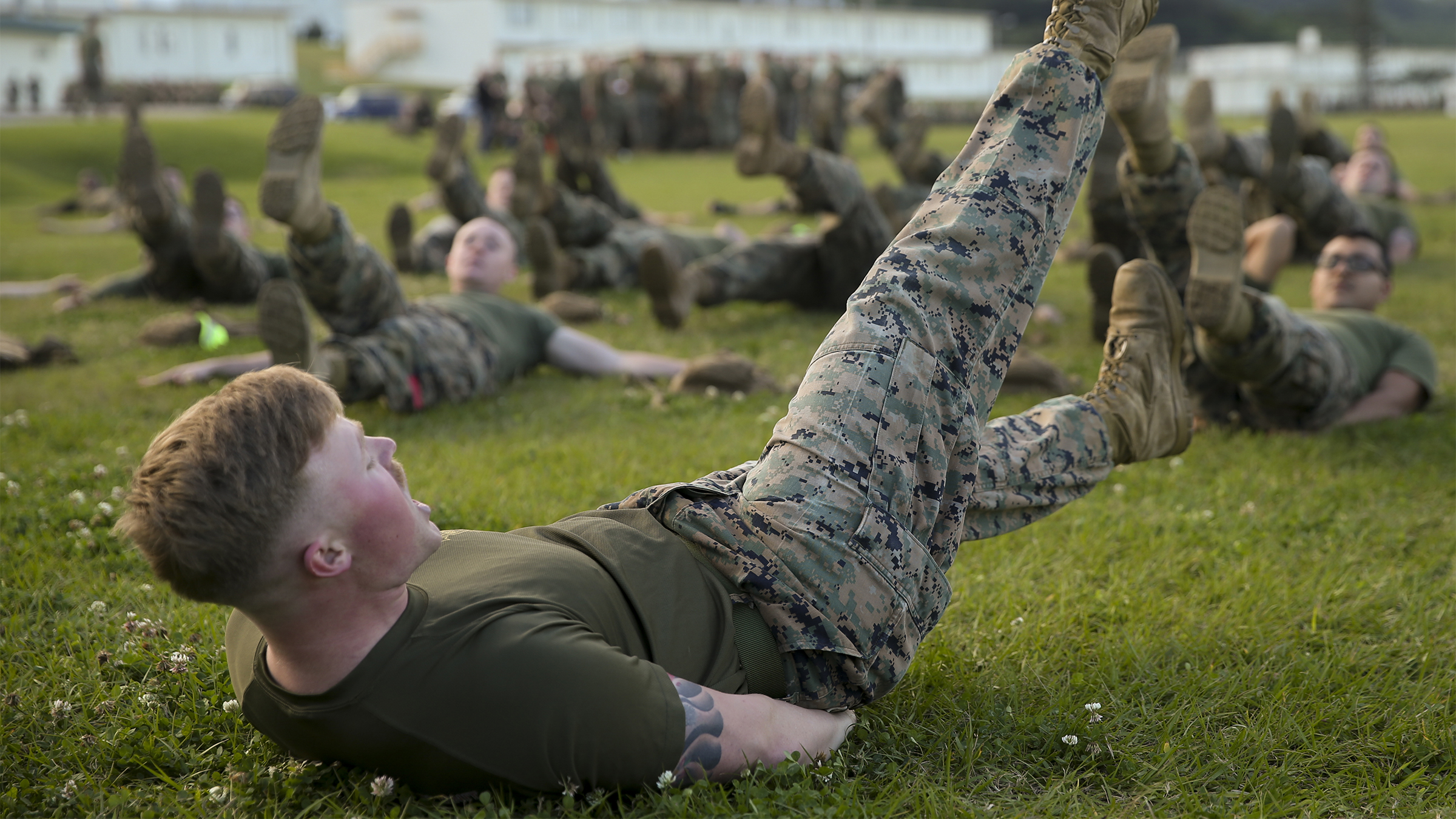 Soldiers working out on grass.