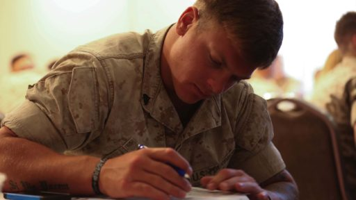 A service member fills out résumé information during an employment and education workshop.