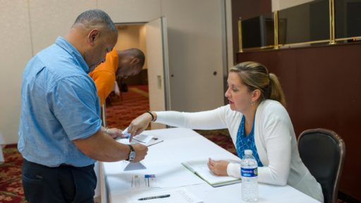 Two people discuss handout during a job fair
