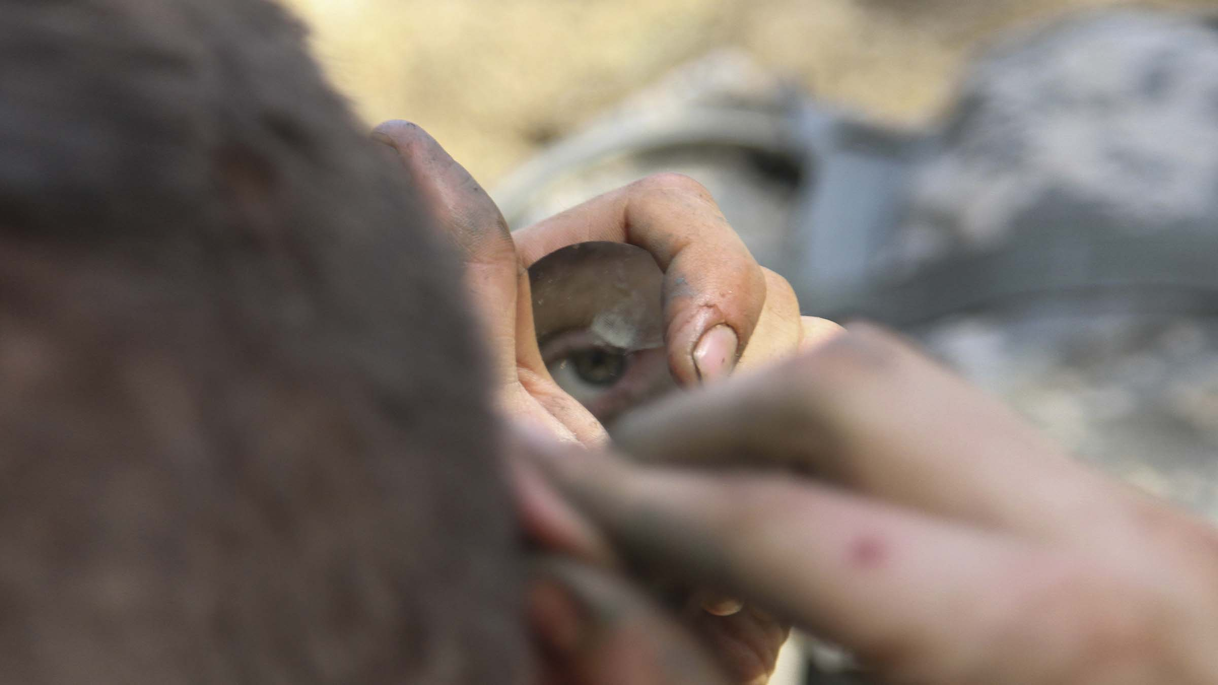Reflected eye of a service member in a tiny mirror as he puts on camo paint.