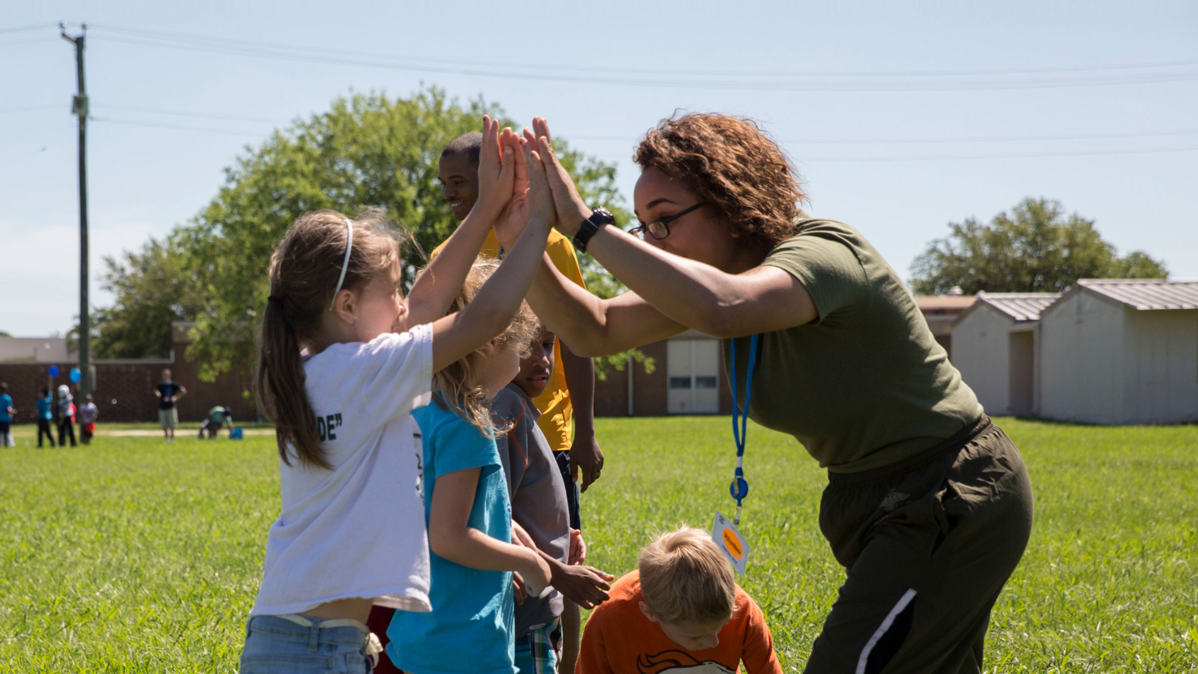 Child high fiving adult at community event