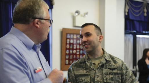 A male Military OneSource state consultant speaks with a male Airman at an event.