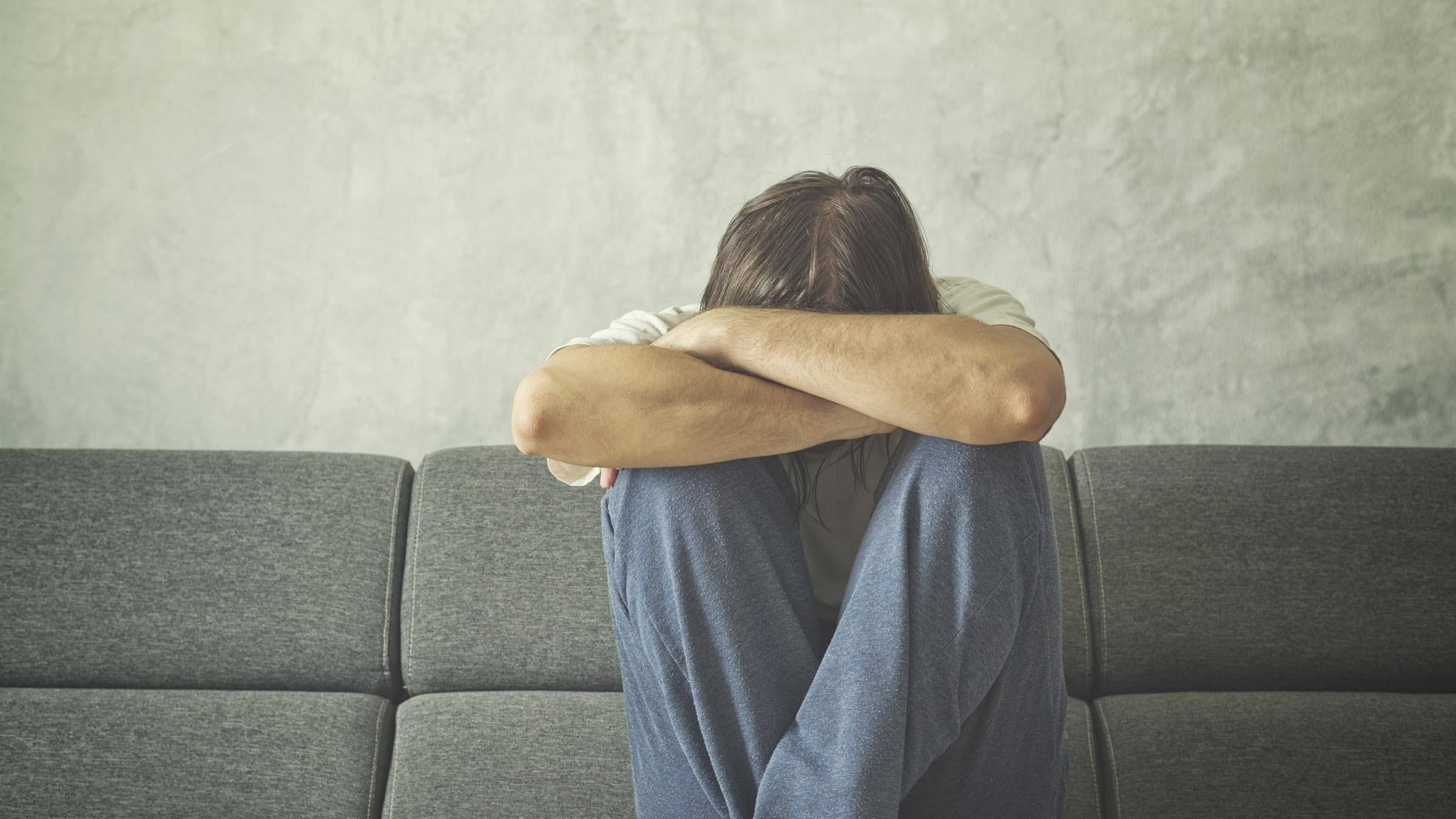 Man on couch with head in arms