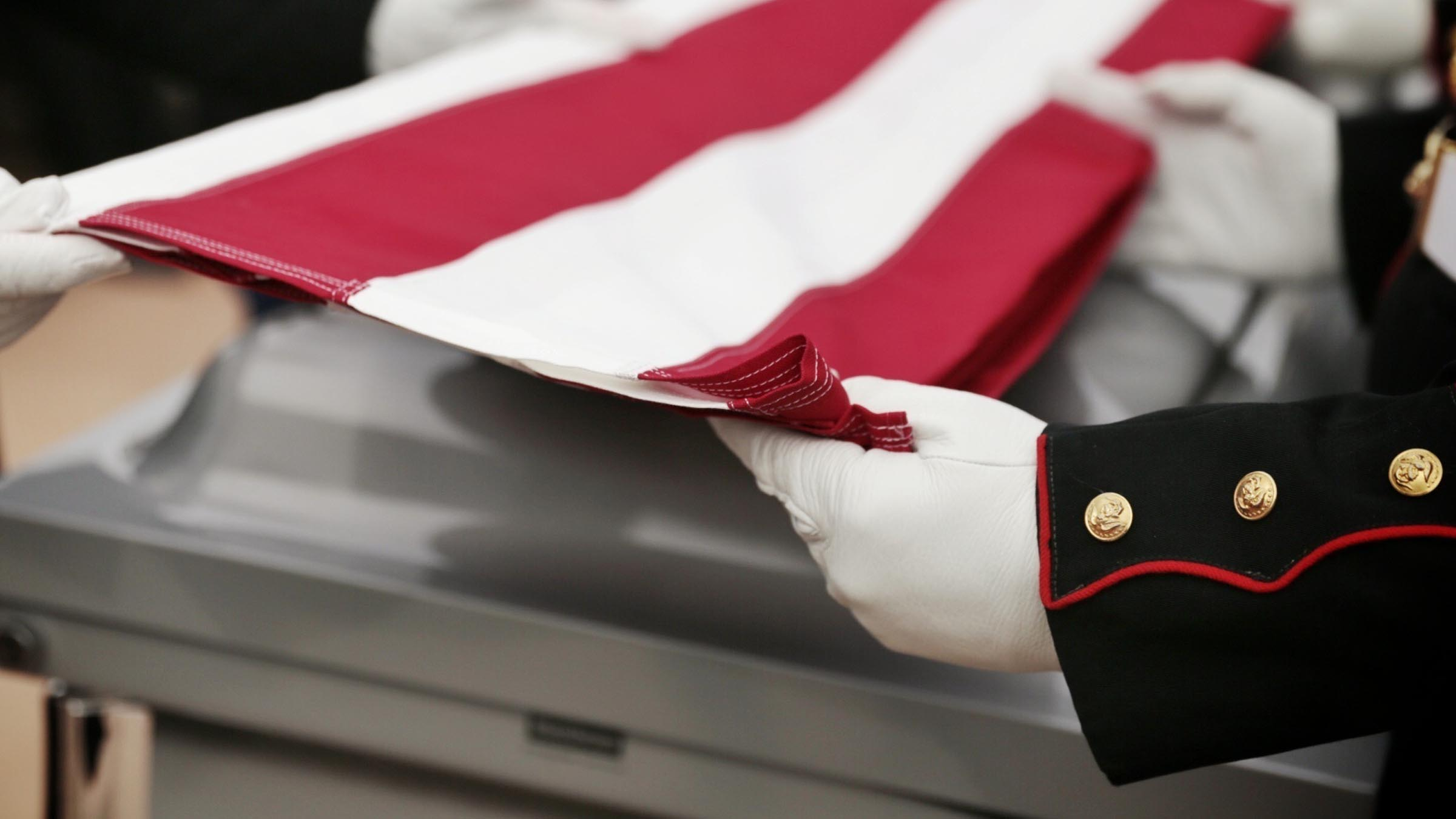 Soldiers folding flag over casket
