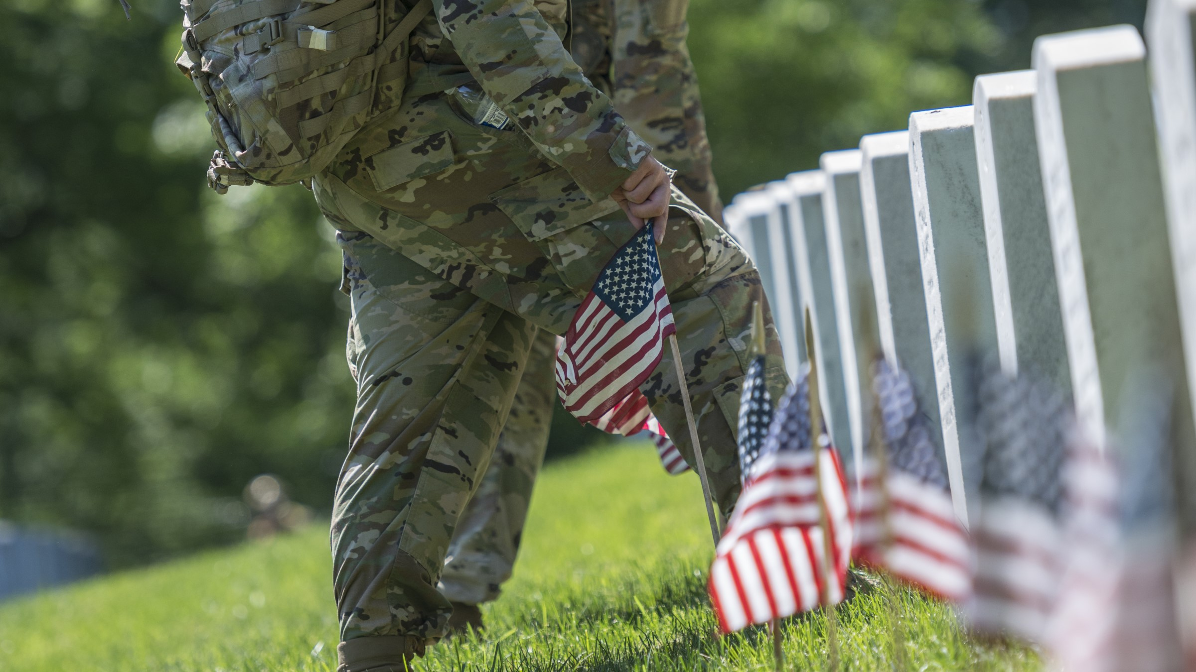 Soldiers place U.S. flags in headstones at Arlington National Cemetery, VA.