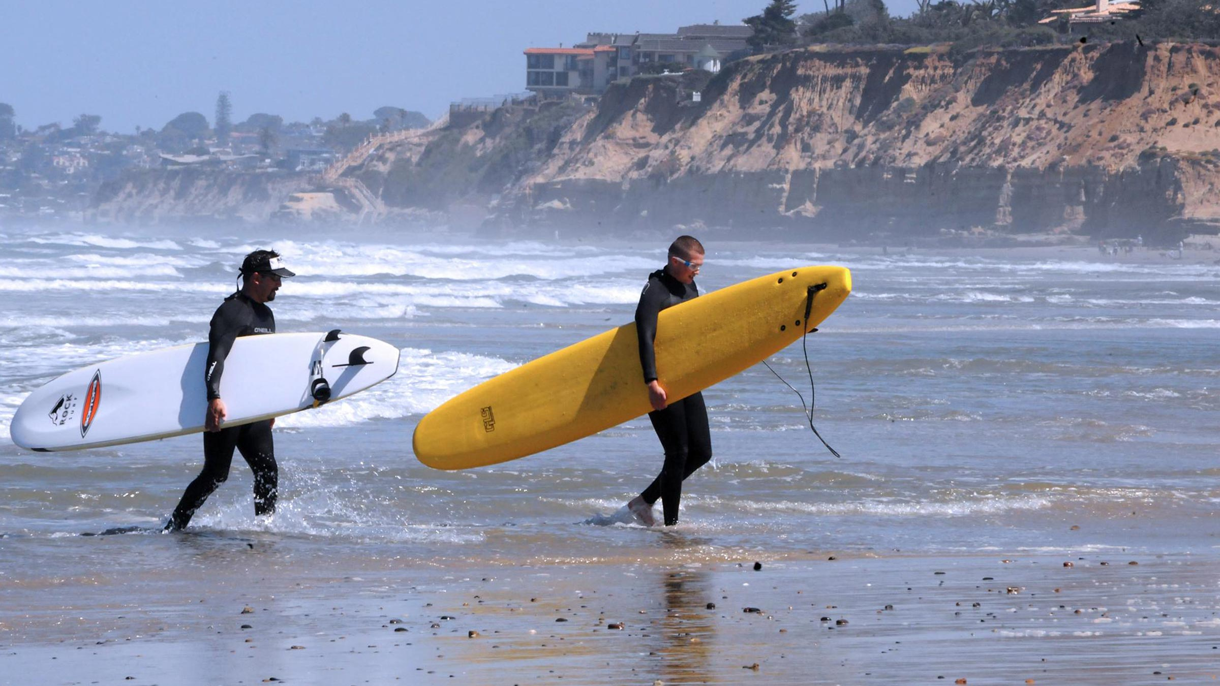 Two men leave the water after a surfing lesson
