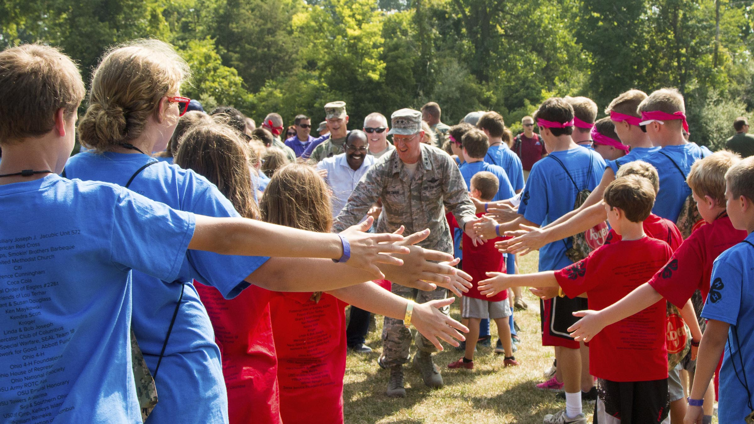 Kids at camp high fiving service member