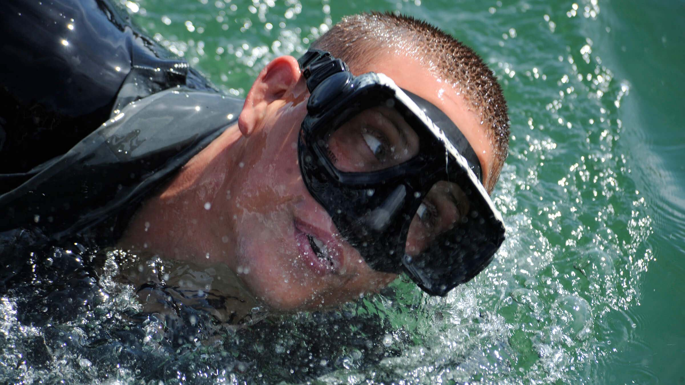 Navy Basic Crewman Training candidate takes a breath during a conditioning swim