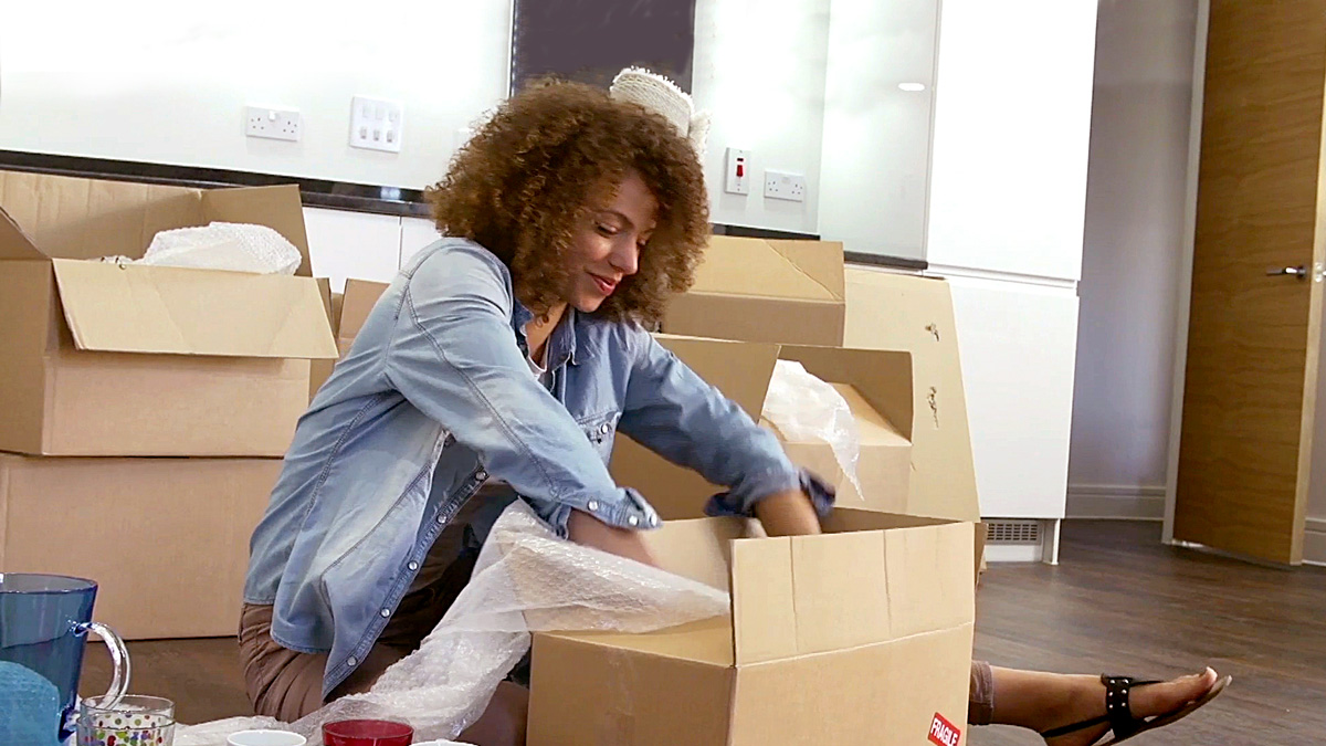Woman packs moving box